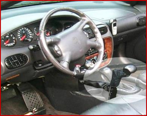 Photo shows that controls can be mounted for the left or right hand. Pictured here is a right-floor-mounted mechanical hand control. Also a removable accelerator pedal block and steering wheel spinner knob can be seen. Photo courtesy of Shepherd Center.