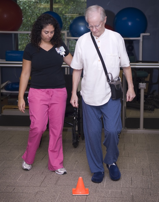 Nurse helping elderly man walk