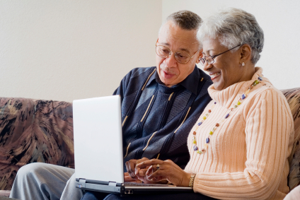 Older African American couple looking at laptop computer together