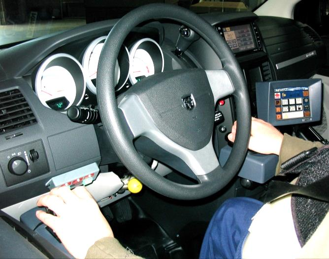 Photo of an Electronic Gas/Brake Lever used with left arm and Electronic Wheel used with right arm for steering.
