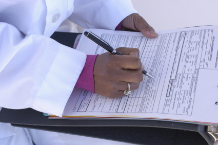 Female doctor writing notes in patient chart