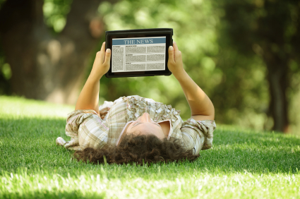 man laying on grass reading news on a tablet computer