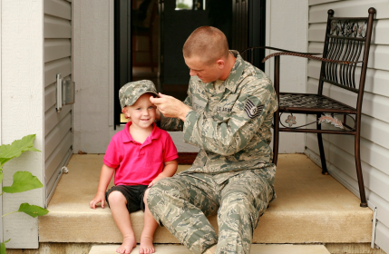 Military father putting his hat on his son