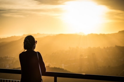Silhouette of a person looking at a setting sun