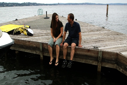 Two people sitting on a pier.