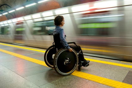 Person in a wheelchair in a subway station as a train rushes past