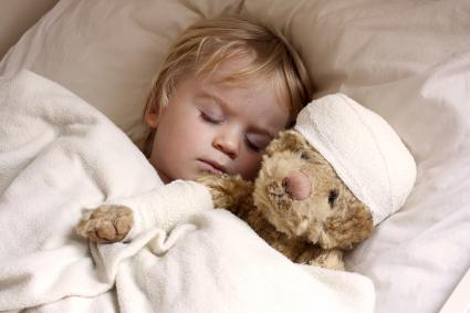 Child sleeping next to a teddy bear