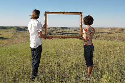 Two people holding a large picture frame showing the distant landscape