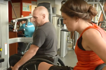 Man and woman with SCI working with gym equipment