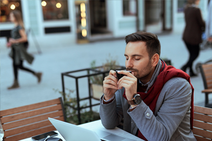 Man at cafe smelling cup of coffee