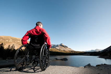 Person on manual wheelchair looking out over a lake