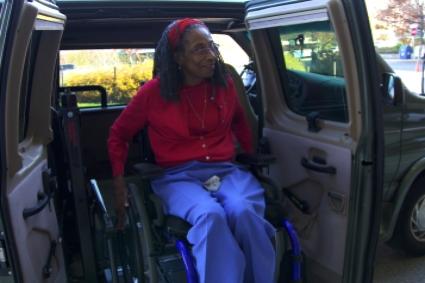 Mujer mayor en silla de ruedas saliendo de la camioneta