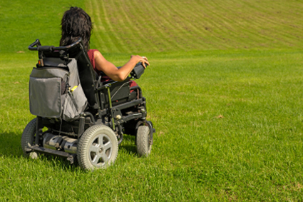Woman on a wheelchair in a large field