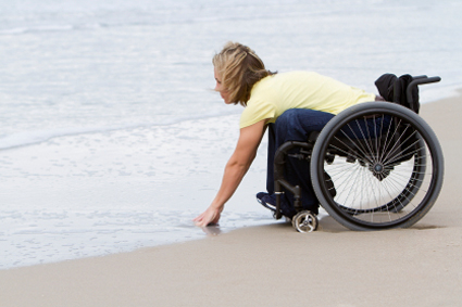 Person in a wheelchair on the beach, leaning down to touch the water