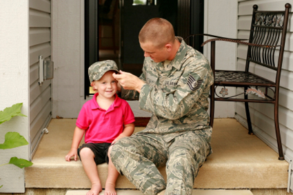 Military father putting his hat on his child