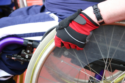 A person sitting in a wheelchair, grasping the wheel with a gloved hand