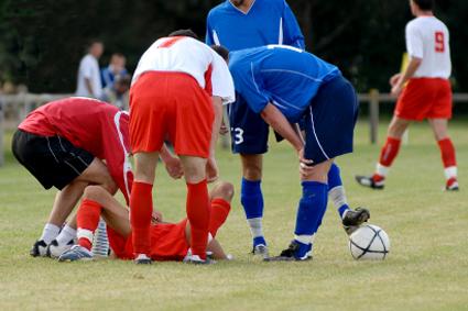 Soccer players huddled around injured teammate