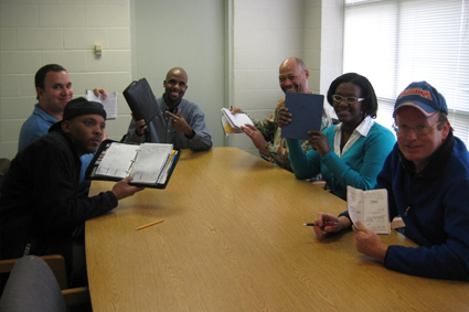 A group of people with notebooks gathered around a conference table