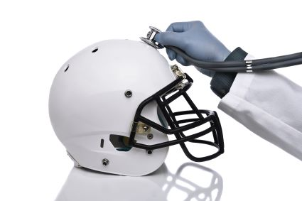 Hand holding a stethoscope to a football helmet