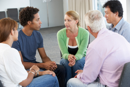 A support group of five people sitting and talking