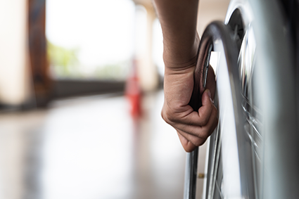 Image of a wheelchair wheel with a hand on it