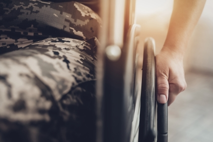 Person in military uniform sitting in a wheelchair.