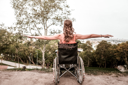 Person sitting in wheelchair looking at view with arms raised out to the sides.