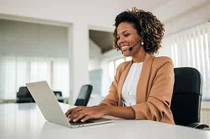 Woman sitting at laptop, talking on camera