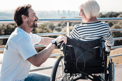 A smiling young man crouching next to an older woman in a wheelchair