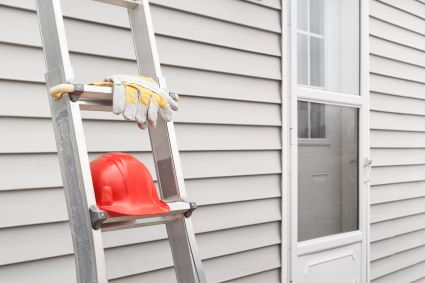 Ladder and hard hat leaning against a wall