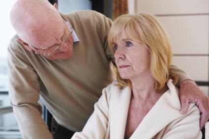 Una mujer mayor, de aspecto triste consolada por su pareja