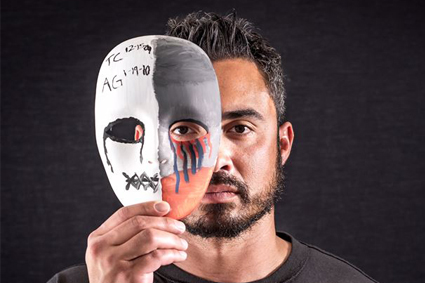 Man holding mask on half of his face