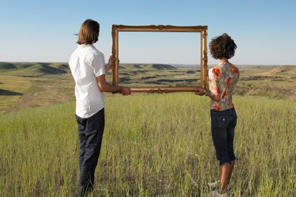 People holding empty picture frame in a field