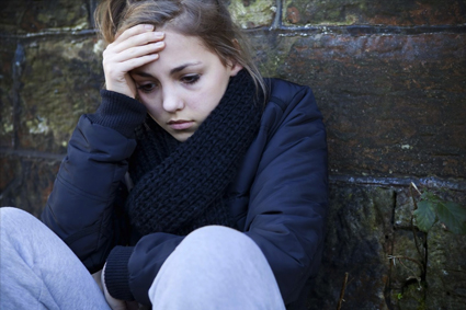 Person leaning against a wall looking upset