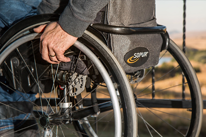 Hand resting on wheel of wheelchair