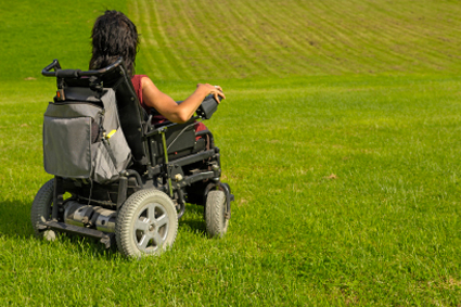 Person using power wheelchair in a grass field